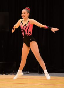 An aerobics gymnast performing in a black, coral and mesh leotard with a flame design