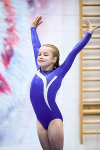 A gymnast salutes to the judges in a blue and white leotard