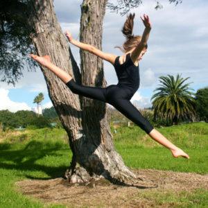A gymnast leaps, wearing a black leotard and black 3/4 leggings