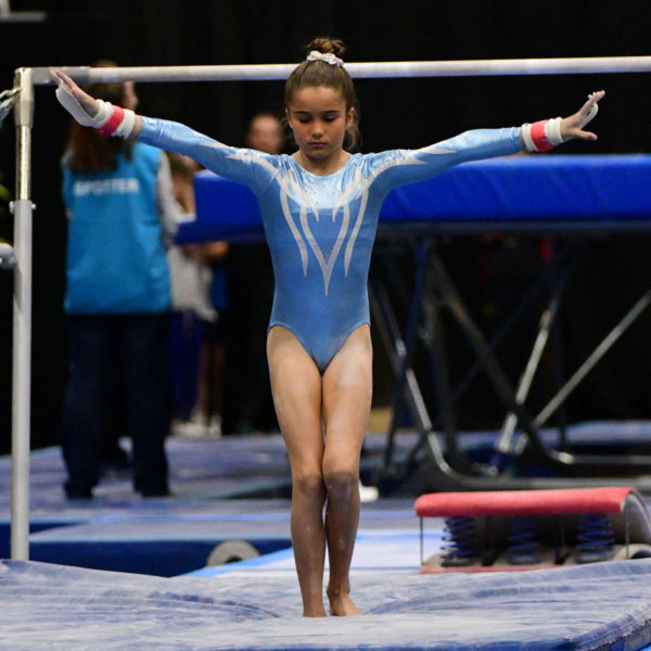 A gymnast lands her bar routine wearing a light blue long sleeve leotard with a white design on the front